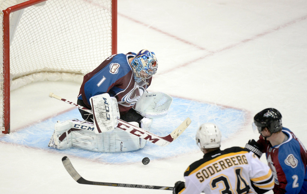 . Colorado goaltender Semyon Varlamov covered up a loose puck as Boston center Carl Soderberg (34) skated toward the crease in the second period. The Colorado Avalanche hosted the Boston Bruins at the Pepsi Center Friday night, March 21, 2014. (Photo by Karl Gehring/The Denver Post)