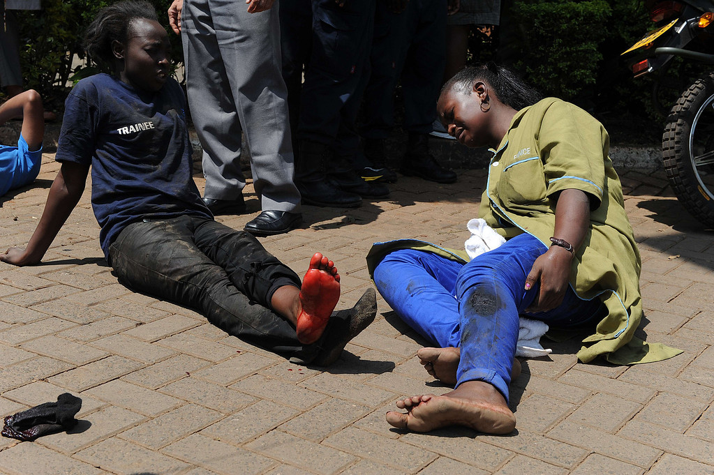 . Injured people sit on the street waiting for assistance after masked gunmen stormed an upmarket mall and sprayed gunfire on shoppers and staff, killing at least thirteen on September 21, 2013 in Nairobi. T AFP PHOTO/SIMON  MAINA/AFP/Getty Images