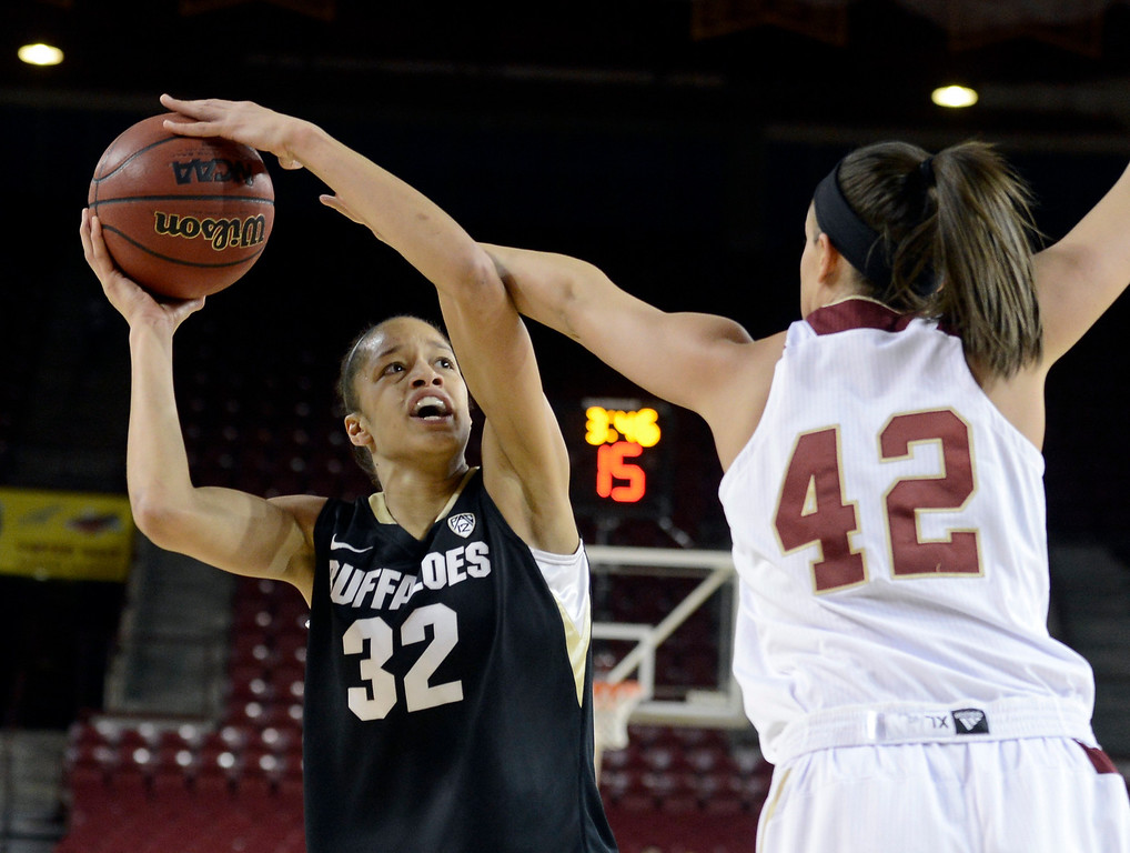 . University of Colorado\'s Arielle Roberson takes a shot over Alison Janecek during a games against the University of Denver on Tuesday, Dec. 11, at the Magnus Arena on the DU campus in Denver.   (Jeremy Papasso/Daily Camera)