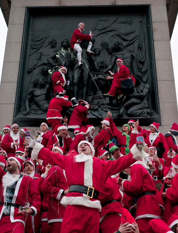 . This Dec. 11, 2010 file photo shows people dressed in Santa Claus outfits at Trafalgar Square in London as part of the annual Santacon. SantaCon is coming to town _ in fact, to nearly 300 towns and cities around the world. Dozens, sometimes hundreds of red-suited revelers gather, barhop, stop traffic and pose for photos.  (AP Photo/Sang Tan, file)