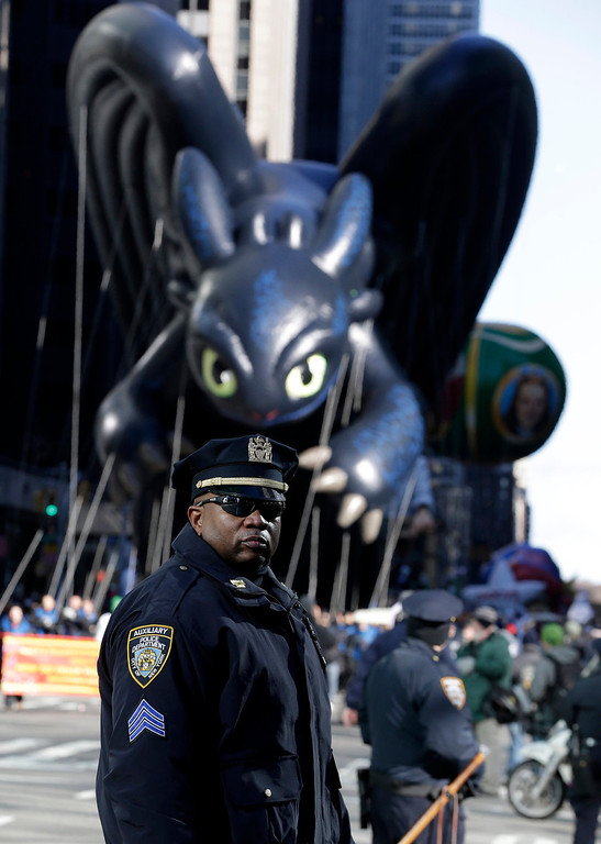 . A police officer stands guard as a balloon flies low because of wind activity during the Macy\'s Thanksgiving Day Parade, Thursday, Nov. 28, 2013, in New York. After fears the balloons could be grounded if sustained winds exceeded 23 mph, Snoopy, Spider-Man and the rest of the iconic balloons received the all-clear from the New York Police Department to fly between Manhattan skyscrapers on Thursday. (AP Photo/Julio Cortez)