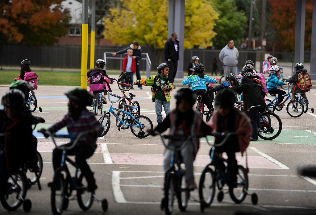 . DENVER, CO - Oct. 11: After being fitted for their helmets and bikes, the students take a spin on the school blacktop. Wish for Wheels and its volunteers build and give away over one hundred bikes to kindergarteners and first-graders at Smith Renaissance School in Park Hill. Wish for Wheels says its goal with one-in-five children liven in poverty, is to give as many kids as possible their first brand new bike and helmet. (Photo By Kathryn Scott Osler/The Denver Post)