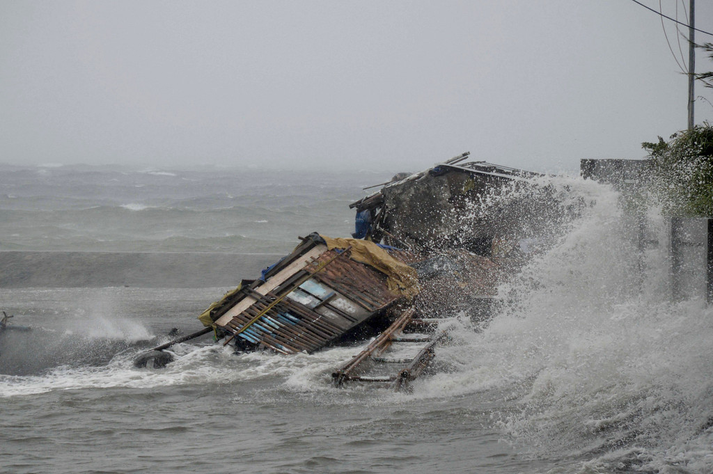 . A house is engulfed by the storm surge brought about by powerful typhoon Haiyan that hit Legazpi city, Albay province Friday Nov.8, 2013 about 520 kilometers ( 325 miles) south of Manila, Philippines.  (AP Photo/Nelson Salting)