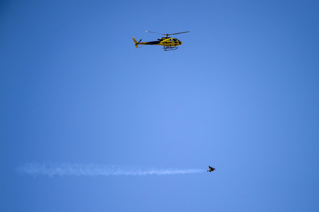 """. Swiss pilot Yves Rossy known as the \""""Jetman\"""" flights beneath a helicopter with his jet-powered two meters wingspan wing attached to his back during the first day of the AIR14 air show on August 30, 2014 in Payerne, western Switzerland.   AFP PHOTO / FABRICE COFFRINI/AFP/Getty Images"""