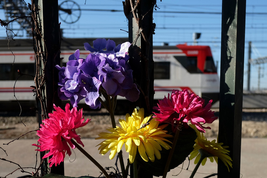 . A train passes by flowers placed on a fence along Tellez street in rememberance of victims of the Madrid train bombings on March 11, 2014 marking the10th year anniversary of the attacks that claimed 191 lives and injured more than 1900 others. On March 11, 2004 at 7:40 am, 10 bombs exploded on board four packed commuter trains in Madrid in an attack claimed by the Al-Qaeda terror network, which said they were punishment for Spain\'s role in the US-led invasion of Iraq.   PEDRO ARMESTRE/AFP/Getty Images