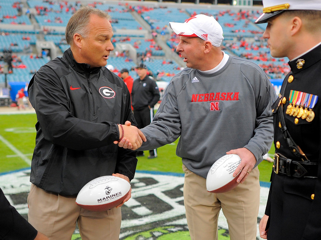 . Georgia head coach Mark Richt, left, and Nebraska head coach Bo Pelini right, greet each other before the start of the Gator Bowl NCAA college football game, Wednesday, Jan. 1, 2014, in Jacksonville, Fla. (AP Photo/Stephen B. Morton)