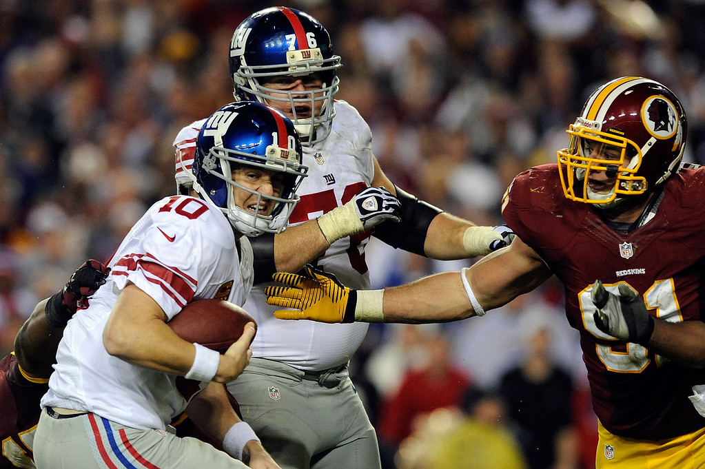 . LANDOVER, MD - DECEMBER 03:  Eli Manning #10 of the New York Giants is sacked by the Washington Redskins during the second half of game at FedExField on December 3, 2012 in Landover, Maryland.  (Photo by Patrick McDermott/Getty Images)