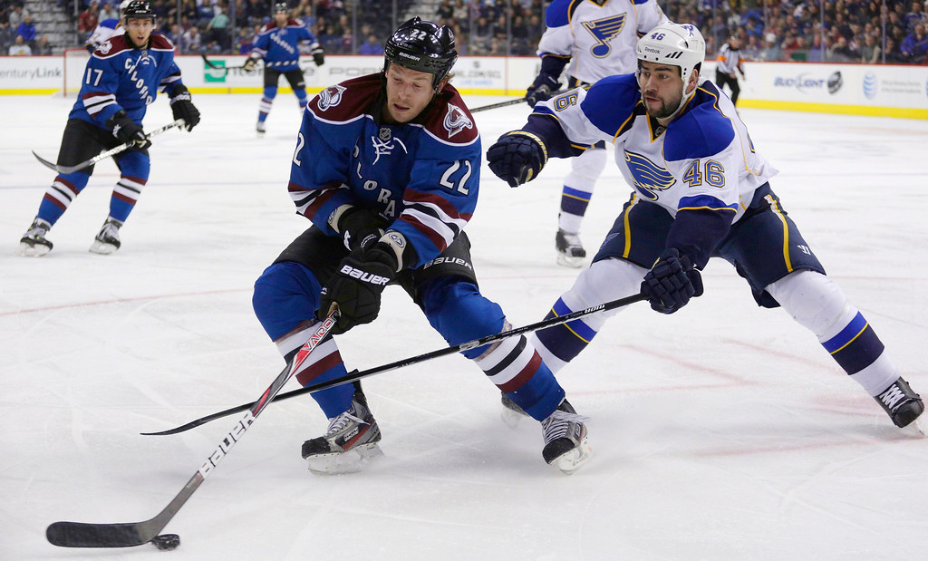 . Colorado Avalanche defenseman Matt Hunwick (22) reaches for the puck against St. Louis Blues defenseman Roman Polak, of the Czech Republic, during the first period of an NHL hockey game, Wednesday, Feb. 20, 2013, in Denver. (AP Photo/Joe Mahoney)