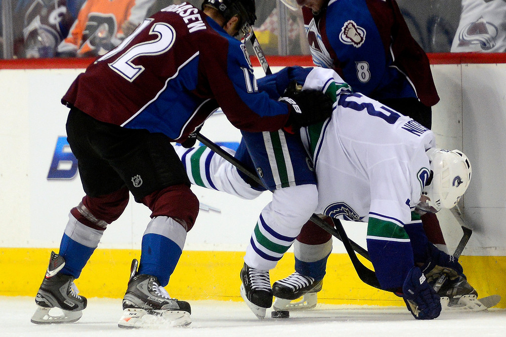 . DENVER, CO - MARCH 24: Chuck Kobasew (12) of the Colorado Avalanche and Jan Hejda (8) defend Kevin Bieksa (3) of the Vancouver Canucks during the first period of action. Colorado Avalanche versus the Vancouver Canucks at the Pepsi Center. (Photo by AAron Ontiveroz/The Denver Post)