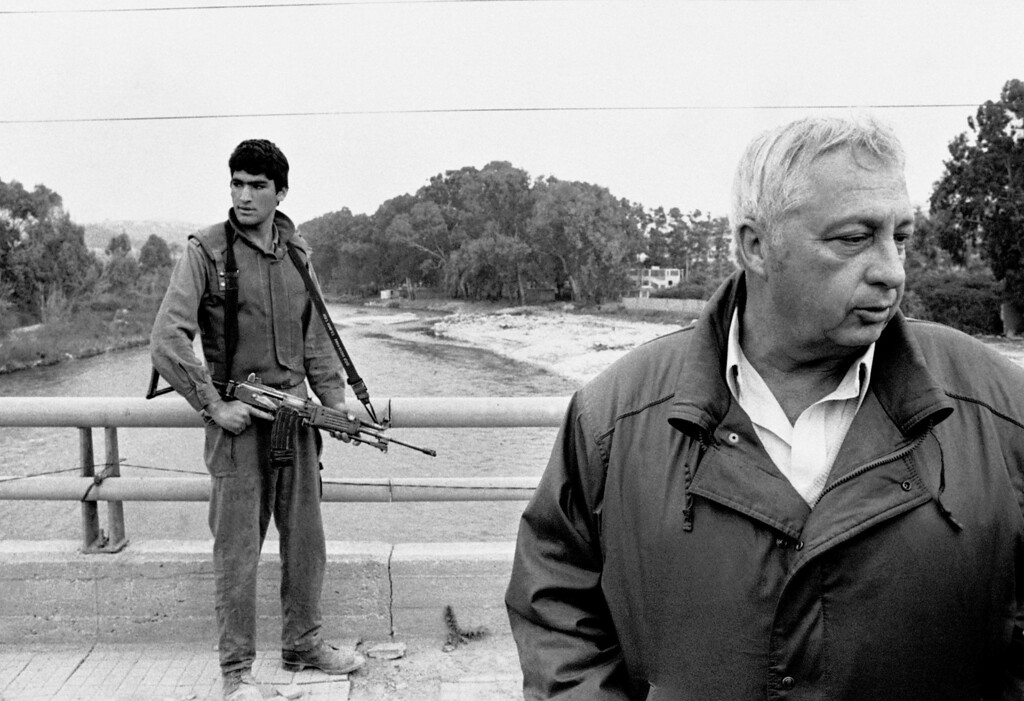 . In this March 7, 1984 file photo, an Israeli soldier keeps his finger on the trigger of his assault rifle while Former Defense Minister Ariel Sharon, right, stands on the bridge overlooking the Awali River, Israel\'s most northerly position in Sidon, Lebanon.  (AP Photo/Max Nash, File)