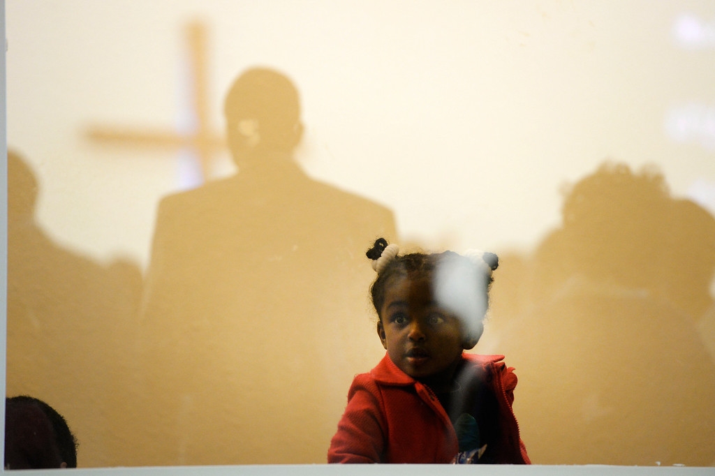 . AURORA, CO. - JANUARY 11:  Lewit Gelaye, 3, peers behind the glass during the Addis Kidan Evangelical Church dedication, Saturday morning, January 10, 2014. (Photo By Andy Cross / The Denver Post)