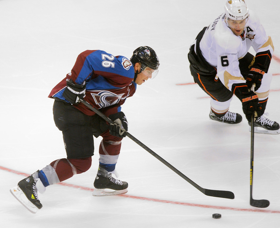. Colorado center Paul Stastny (26) tried to move the puck past Anaheim defenseman Ben Lovejoy (6) in the second period.   Photo By Karl Gehring/The Denver Post