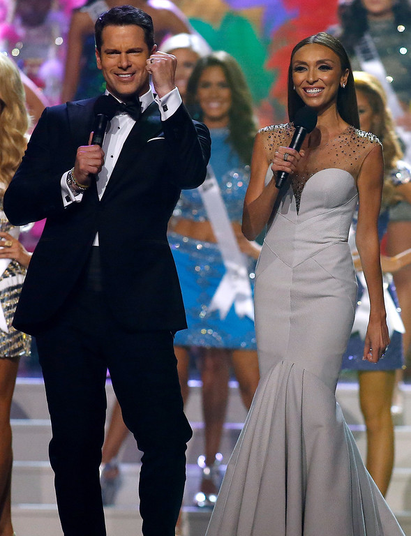 . Hosts Thomas Roberts, left, and Giuliana Rancic welcome contestants to the stage during the Miss USA 2014 pageant in Baton Rouge, La., Sunday, June 8, 2014. (AP Photo/Jonathan Bachman)