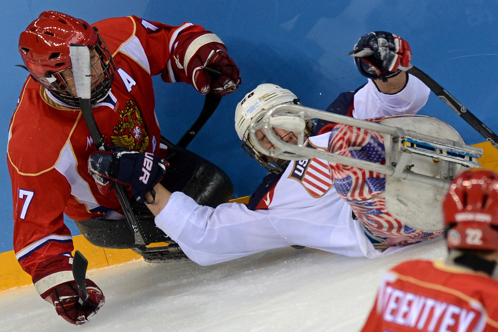 . United States\' Rico Roman (R) vies with Russia\'s Vadim Selyukin during Sledge Hockey Final match between Russia and USA at XI Paralympic Olympic games in the Shayba stadium close near Sochi on March 15, 2014. AFP PHOTO/KIRILL KUDRYAVTSEV/AFP/Getty Images