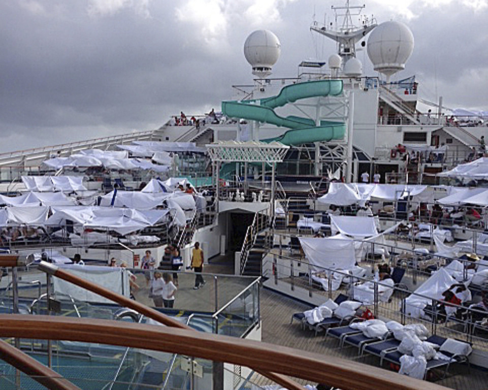 . This Sunday, Feb. 10, 2013 photo, provided by Kalin Hill, of Houston, shows passengers with makeshift tents on the the deck of the Carnival Triumph cruise ship at sea in the Gulf of Mexico. The ship nearing Mobile Bay is without engine power and is being towed by tugboats. (AP Photo/Kalin Hill)