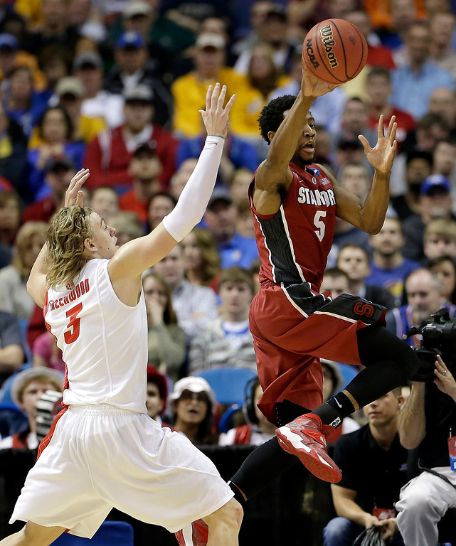 . Stanford\'s Chasson Randle (5) gets past New Mexico\'s Hugh Greenwood to put up a shot during the second half of a second-round game in the NCAA college basketball tournament, Friday, March 21, 2014, in St. Louis. Stanford won the game 58-53. (AP Photo/Charlie Riedel)