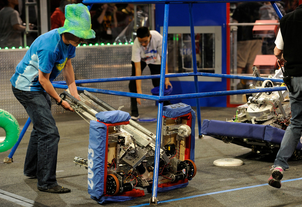 . DENVER, CO.- APRIL 6: Members of the pit crew set things right after one robot tips over. The Colorado Regional FIRST Robotics Competition takes place in Magness Arena inside the Ritchie Center on the University of Denver campus. High School students from all over the state, region, and even a team from Mexico, participate in a high-tech spectator sporting event (this year the teams used frisbees) using specially engineered robots that are maneuvered by human drivers using computers and joy sticks.(Photo By Kathryn Scott Osler/The Denver Post)
