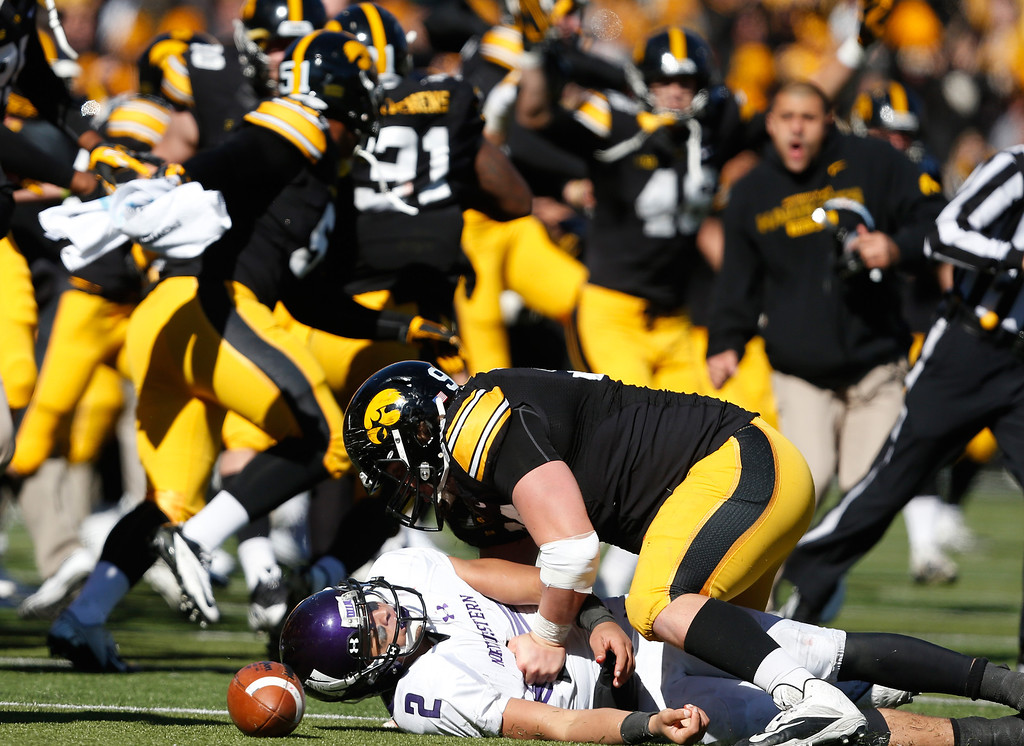 . Iowa player celebrate after defensive lineman Louis Trinca-Pasat (90) brought down Northwestern quarterback Kain Colter (2) on fourth down to seal their 17-10 win in overtime in an NCAA college football game Saturday, Oct. 26, 2013 at Kinnick Stadium in Iowa City, Iowa.  (AP Photo/Brian Ray)