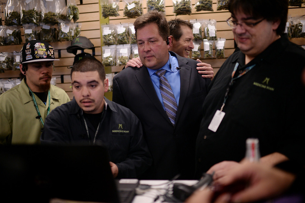. DENVER, CO. JANUARY 01: From left, Ryan Luck, manager Pete Vasquez, president Andy Williams, chief operating officer Pete Williams and Nelson Figueiredo gather around a check-out register at Medicine Man  recreational marijuana dispensary on New Years day in Denver, Colorado, January 1, 2014. Medicine Man marijuana dispensary is one of a handful of stores that started selling legal recreational-marijuana on January 1,  2014. Colorado is the first place in the modern world with a regulated marijuana market. (Photo by Hyoung Chang/The Denver Post)