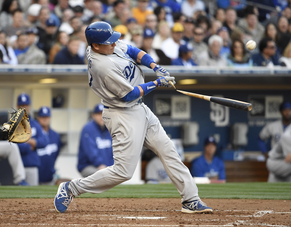 . A.J. Ellis #17 of the Los Angeles Dodgers breaks his bat as he hits a single during the second inning of a baseball game against the San Diego Padres on Opening Night at Petco Park on March 30, 2014 in San Diego, California.  (Photo by Denis Poroy/Getty Images)