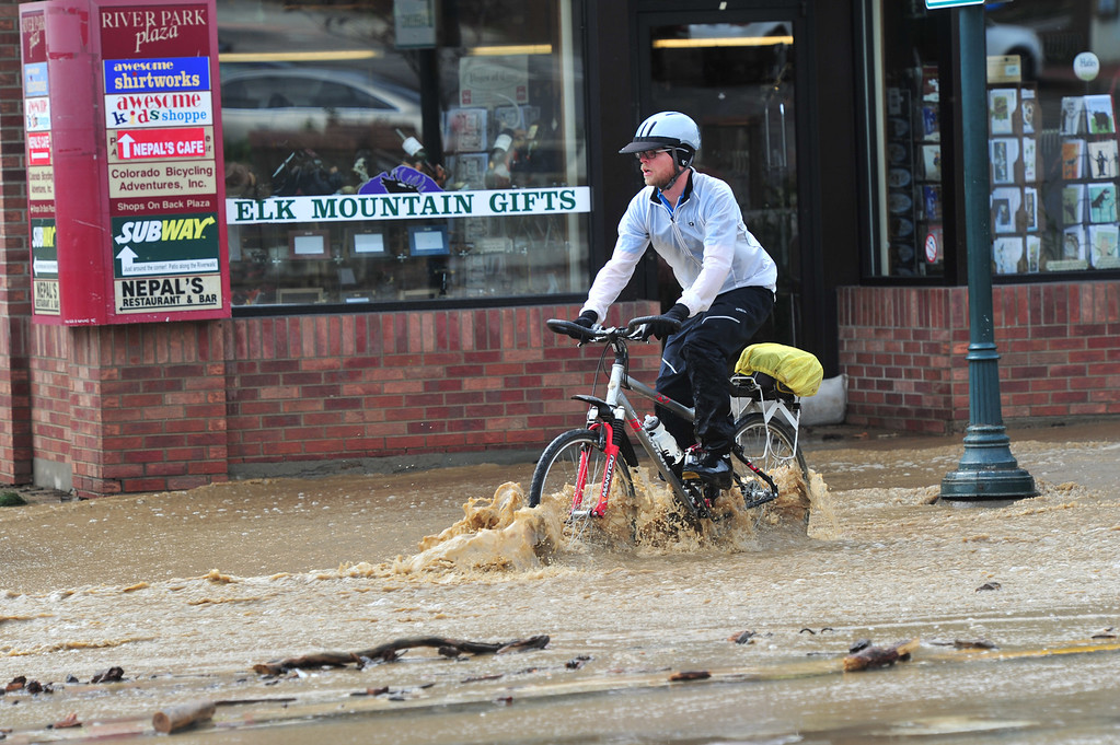 . A cyclist attempts a ride down Elkhorn Avenue on Friday morning, September 13, 2013. By Saturday, the ride was much easier as the rivers receded. Walt Hester/Estes Park Trail-Gazette