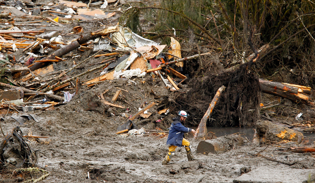 . A searcher walks through mud near a massive pile of debris at the scene of a deadly mudslide, Thursday, March 27, 2014, in Oso, Wash.  (AP Photo/The Herald, Mark Mulligan, Pool)