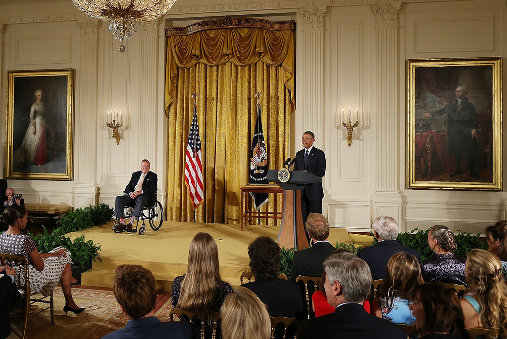 . U.S. President Barack Obama speaks while flanked by former President George H. W. Bush (L) who is sitting in a wheelchair, during an event in the East Room at the White House, July 15, 2013 in Washington, DC. Bush joined President Obama in hosting the event to honor the 5,000th Daily Point of Light Award winner.  (Photo by Mark Wilson/Getty Images)