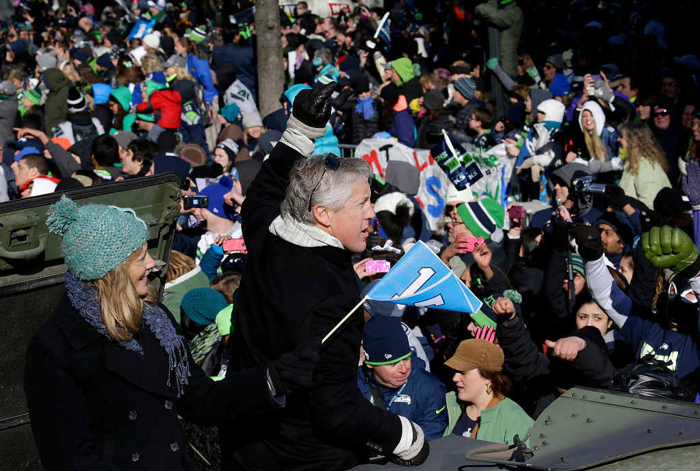 . Seattle Seahawks head coach Pete Carroll, center, waves with his wife Glena during the Super Bowl champions parade on Wednesday, Feb. 5, 2014, in Seattle.  (AP Photo/Ted S. Warren)