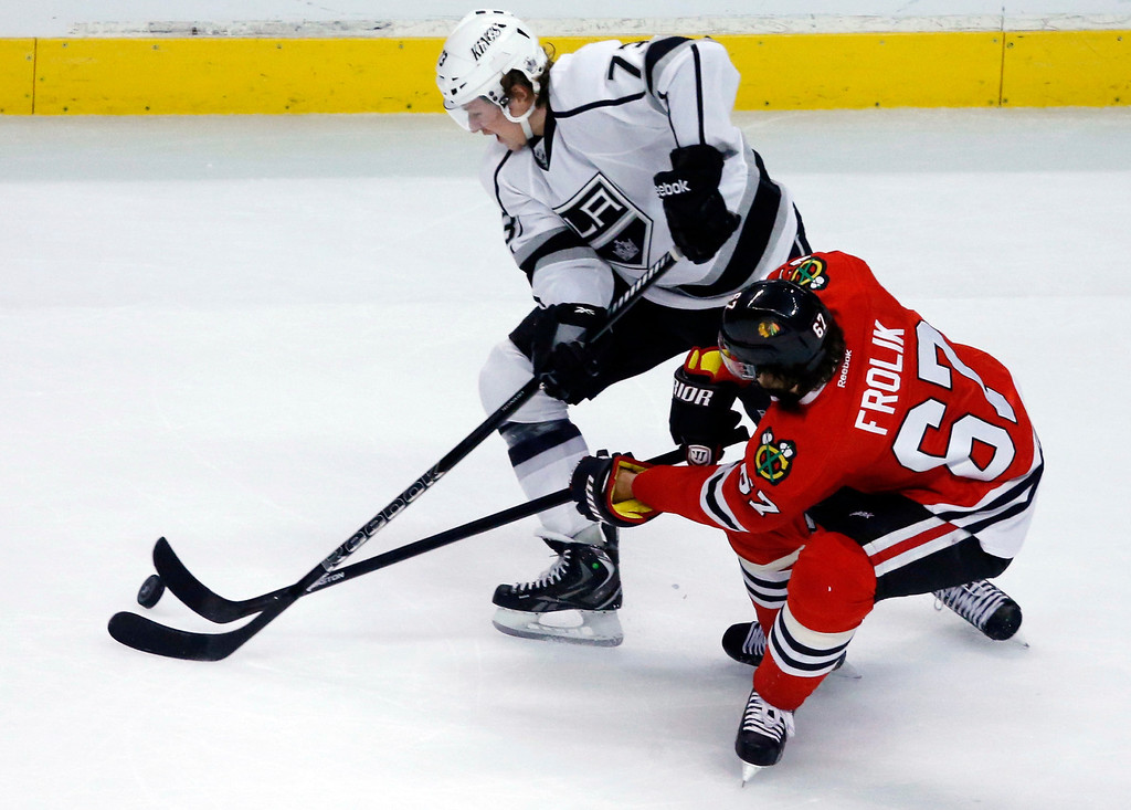 . Los Angeles Kings center Tyler Toffoli (73) and Chicago Blackhawks center Michael Frolik (67) reach for the puck during the first period in Game 5 of the NHL hockey Stanley Cup playoffs Western Conference finals Saturday, June 8, 2013, in Chicago. (AP Photo/Charles Rex Arbogast)