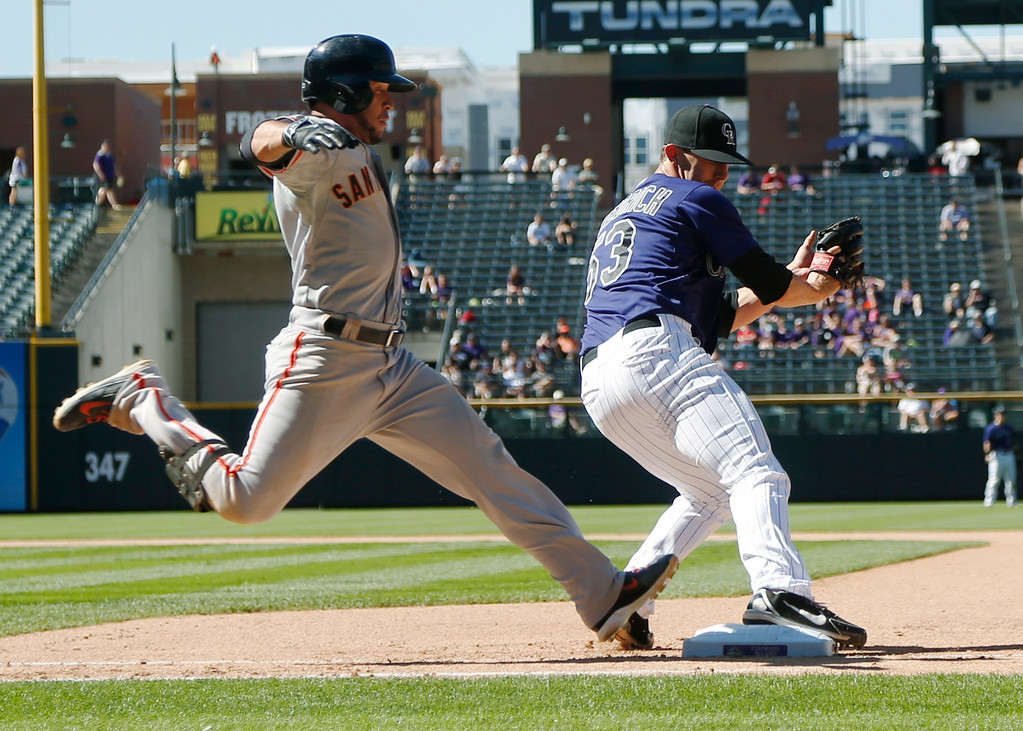 . San Francisco Giants\' Gregor Blanco, left, is out at first base as Colorado Rockies relief pitcher Christian Friedrich fields throw from second baseman DJ LeMahieu during the seventh inning of the Rockies\' 9-2 victory in a baseball game in Denver on Wednesday, Sept. 3, 2014. (AP Photo/David Zalubowski)