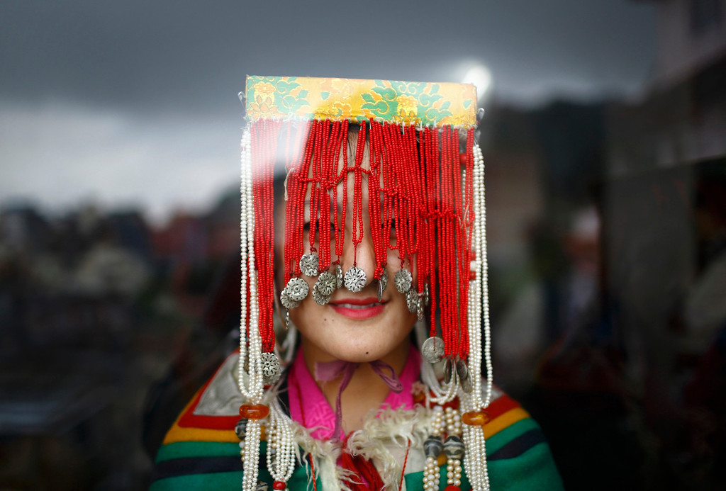 . A Tibetan girl in traditional costume is pictured through the window of a monastery during celebrations of the 78th birthday of exiled spiritual leader Dalai Lama in Kathmandu July 6, 2013. During last month\'s visit of Chinese State Councilor Yang Jiechi, Chairman of the Interim Election Council Khil Raj Regmi said Nepal is firmly committed to the One-China Policy and reaffirmed its stand that the territory of Nepal will not be allowed to be used for any activities against China. Nepal ceased issuing refugee papers to Tibetans in 1989 and recognizes Tibet to be a part of China. REUTERS/Navesh Chitrakar