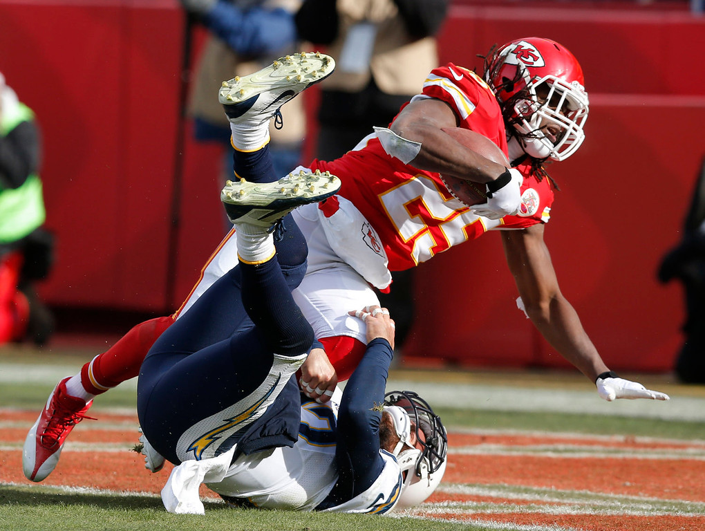 . Kansas City Chiefs running back Jamaal Charles (25) scores a touchdown over San Diego Chargers free safety Eric Weddle during the first half of an NFL football game at Arrowhead Stadium in Kansas City, Mo., Sunday, Nov. 24, 2013. (AP Photo/Ed Zurga)