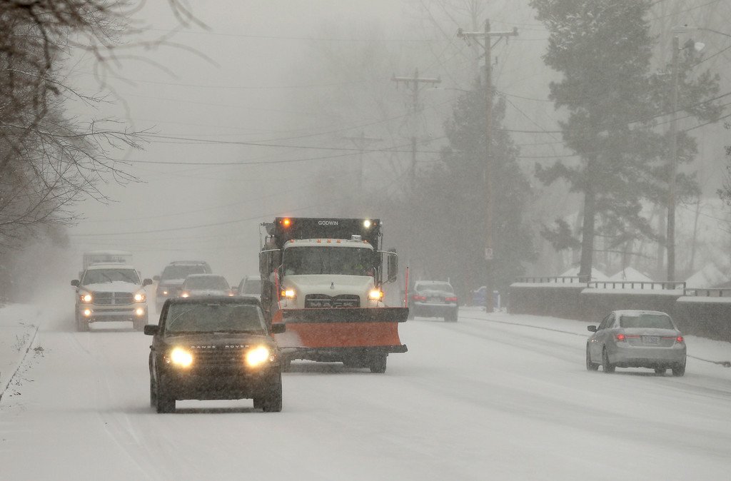 . A truck carrying salt and slag moves slowly down a snow covered road as a winter storm moves into the area in Charlotte, N.C., Wednesday, Feb. 12, 2014. (AP Photo/Chuck Burton)