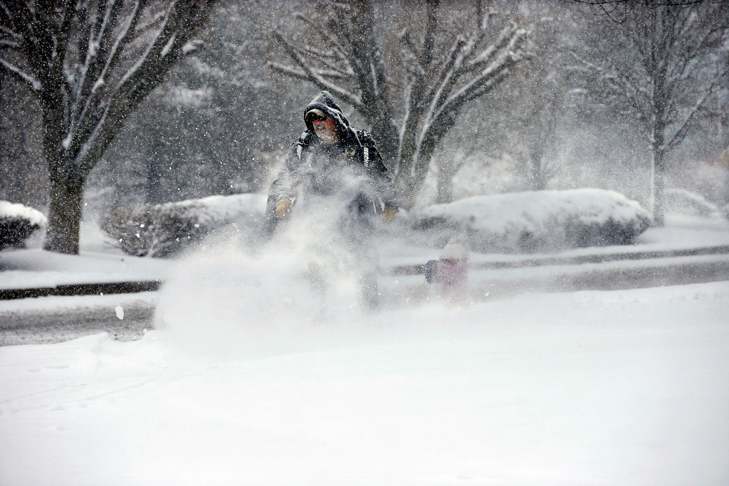 . A man clears snow along a street in Newtown, Pa., Friday, March 8, 2013. A lingering storm that began Wednesday, has left some flooding and snow in the region. Saturday\'s forecast calls for temperatures in the 50s. (AP Photo/Mel Evans)