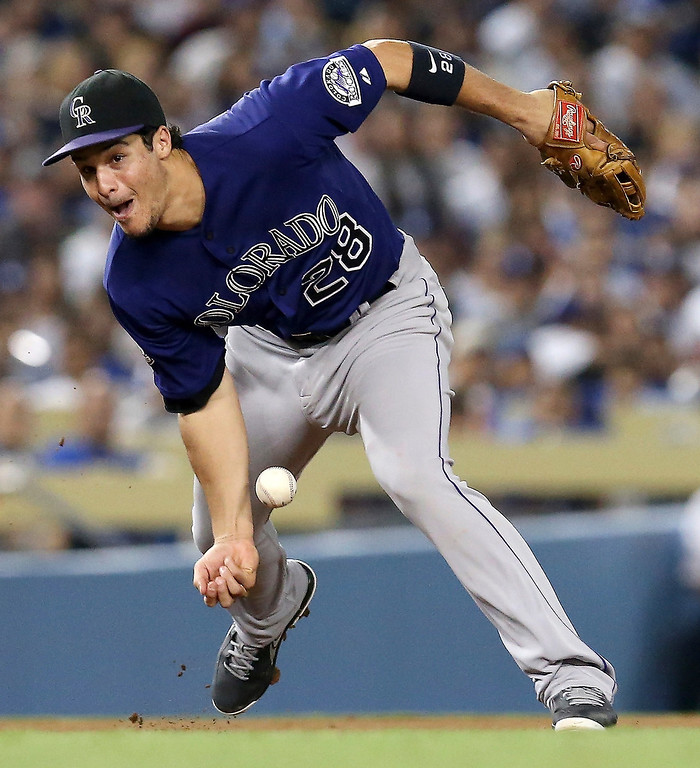 . Third baseman Nolan Arenado #28 of the Colorado Rockies tries to barehand the ball during a game against the Los Angeles Dodgers  on July 11, 2013 in Los Angeles, California.  (Photo by Stephen Dunn/Getty Images)
