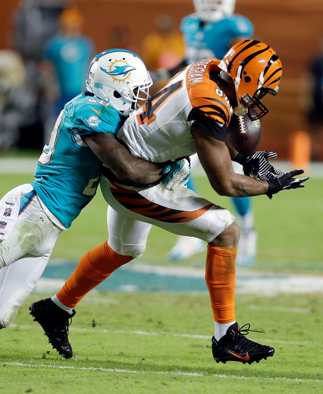 . Miami Dolphins free safety Reshad Jones (20) tackles Cincinnati Bengals tight end Jermaine Gresham (84) during the second half of an NFL football game, Thursday, Oct. 31, 2013, in Miami Gardens, Fla. (AP Photo/Lynne Sladky)