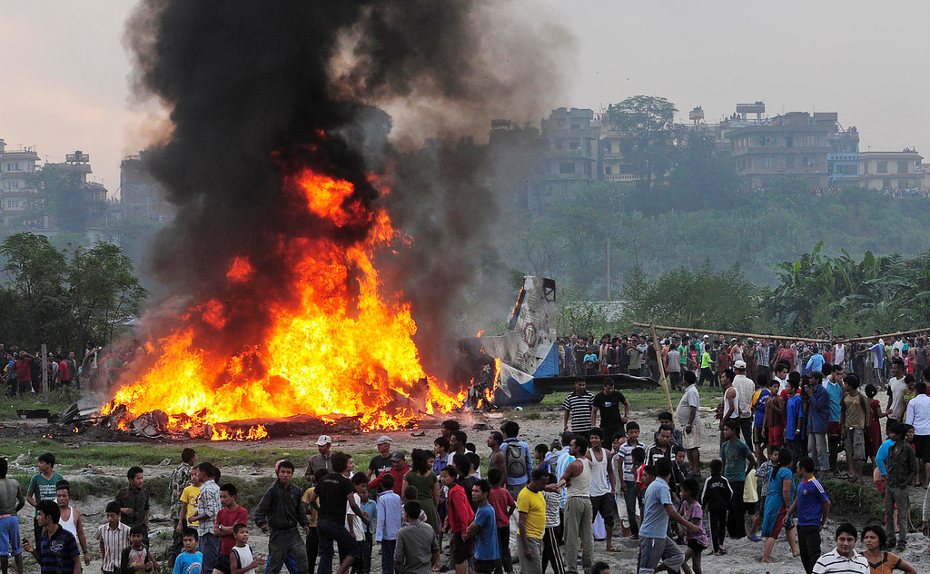 . In this Sept. 28, 2012 file photo, Nepalese gather around the burning wreckage at the crash site of a Sita Air airplane near Katmandu, Nepal. The plane carrying trekkers to the Everest region crashed and burned just after takeoff in Nepal�s capital, killing the 19 Nepali, British and Chinese people on board. (AP Photo/File)