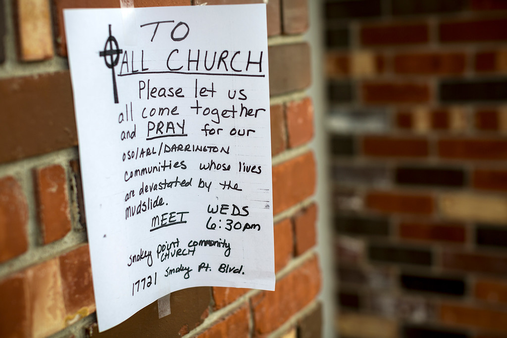. A handwritten note flutters on a storefront as a call for Arlington residents to pray together Thursday, March 27, 2014, in Arlington within Snohomish County, Wash.  (AP Photo/seattlepi.com, Jordan Stead)