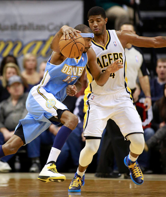 . Denver Nuggets forward Corey Brewer (L) drives on Indiana Pacers forward Paul George during the fourth quarter of an NBA basketball game in Indianapolis, Indiana December 7, 2012.   REUTERS/Brent Smith