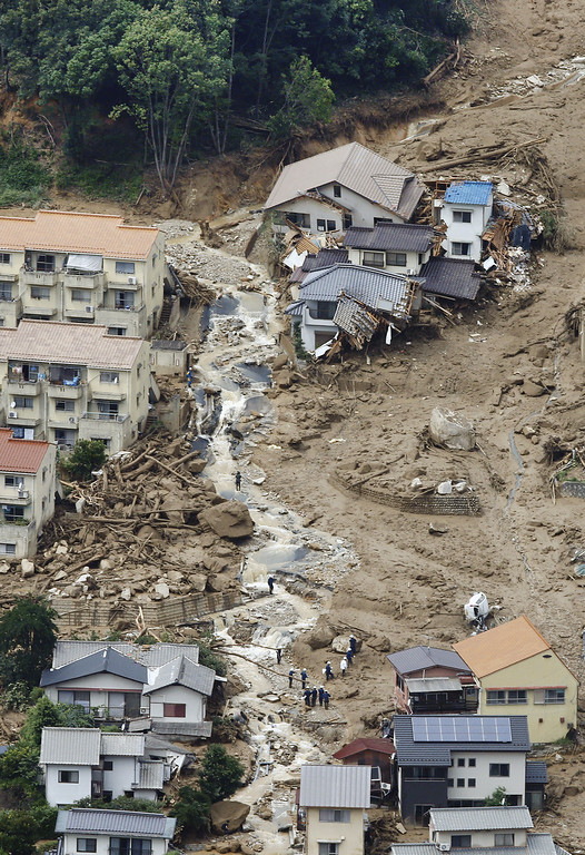 . In this aerial photo, rescue workers are seen on the mud-covered ground as they search for survivors after a massive landslide swept through residential areas in Hiroshima, western Japan, Wednesday, Aug. 20, 2014. (AP Photo/Kyodo News)