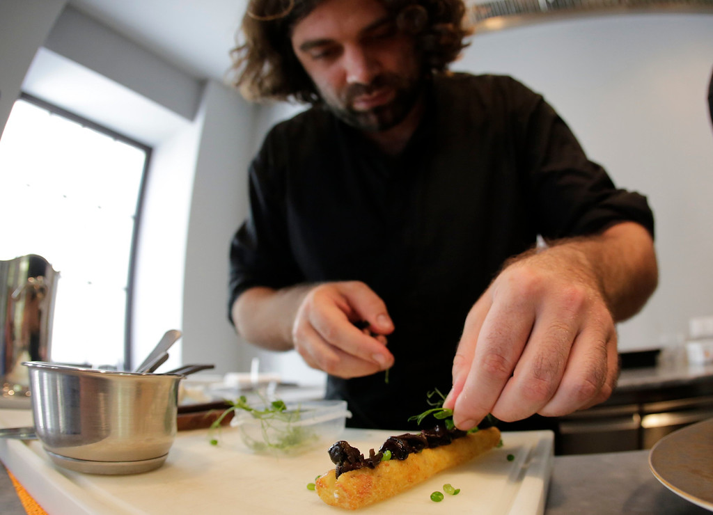 . Austrian chef Konstantin Filippou prepares a snail dish in his gourmet restaurant in Vienna July 12, 2013. Andreas Gugumuck owns Vienna\'s largest snail farm, exporting snails, snail-caviar and snail-liver all over the world. The gourmet snails are processed using old traditional cooking techniques and some are sold locally to Austrian gourmet restaurants. Picture taken July 12, 2013.   REUTERS/Leonhard Foeger