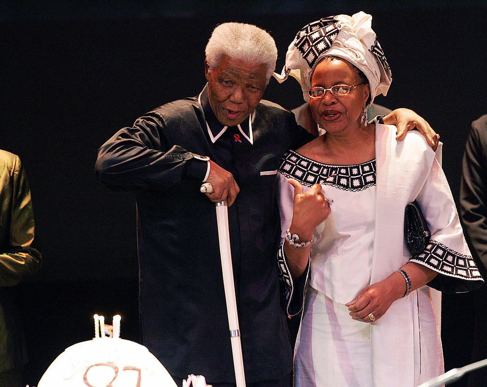 """. Former South African President Nelson Mandela holds his wife Graca Machel while looking at his 87th birthday cake during the third Nelson Mandela Annual Lecture, 19 July 2005 in Johannesburg. Mandela was presented with a white cake with four candles, which he blew out to loud applause from the audience, which sang \""""Happy Birthday\"""" led on by a boisterous Desmond Tutu.    AFP PHOTO/ALEXANDER JOE"""