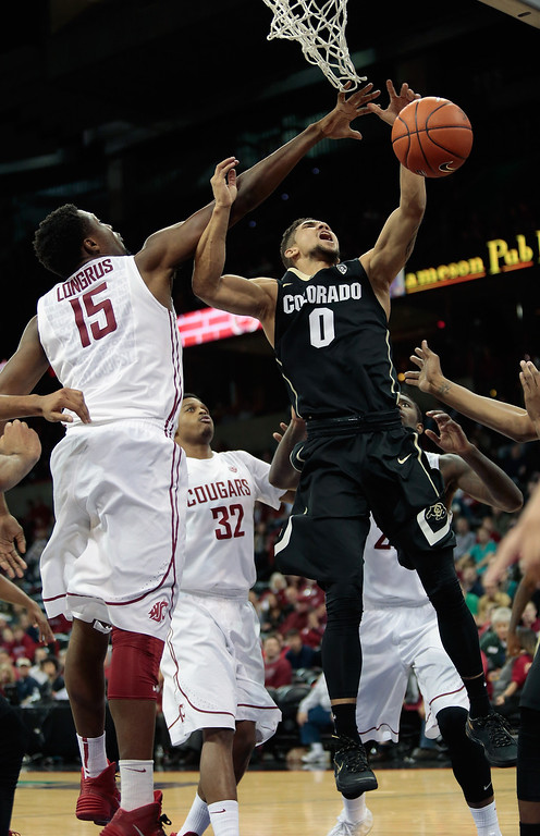 . Askia Booker #0 of the Colorado Buffaloes goes to the basket and is fouled by Junior Longrus #15 of the Washington State Cougars during the game at Spokane Arena on January 8, 2014 in Spokane, Washington.  (Photo by William Mancebo/Getty Images)