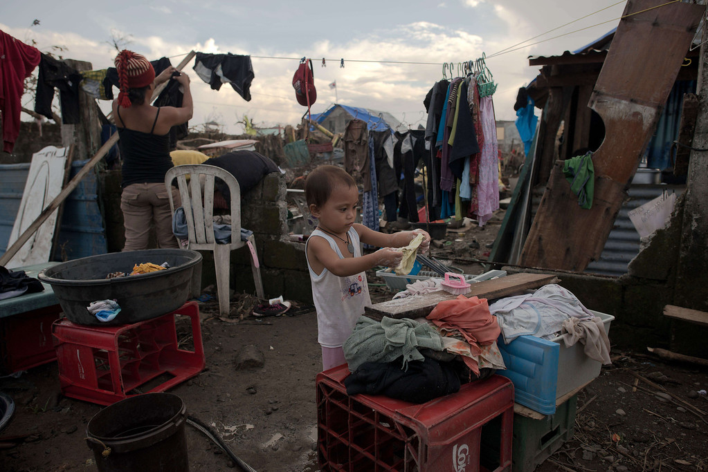 . Typhoon victim Divina (2) helps her mother May (31) to wash their clothes in Palo on November 21, 2013.   AFP PHOTO/ Nicolas ASFOURI/AFP/Getty Images