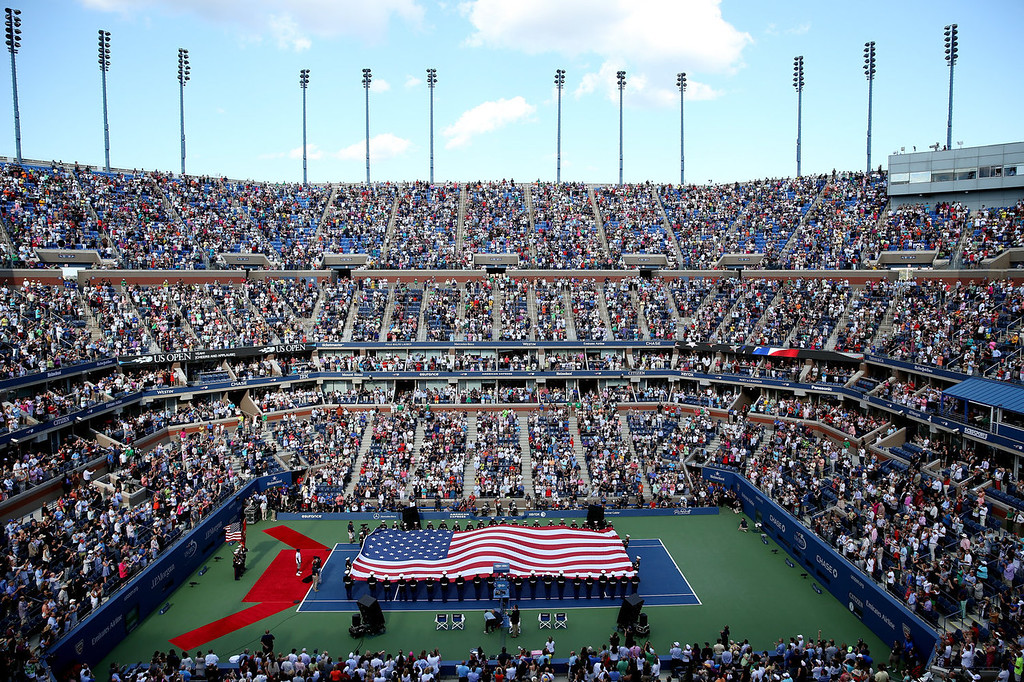 . Arthur Ashe Stadium as military personnel unfurl the national flag before the start of the women\'s singles final match between Victoria Azarenka of Belarus and Serena Williams of the United States of America on Day Fourteen of the 2013 US Open at the USTA Billie Jean King National Tennis Center on September 8, 2013 in the Flushing neighborhood of the Queens borough of New York City.  (Photo by Matthew Stockman/Getty Images)