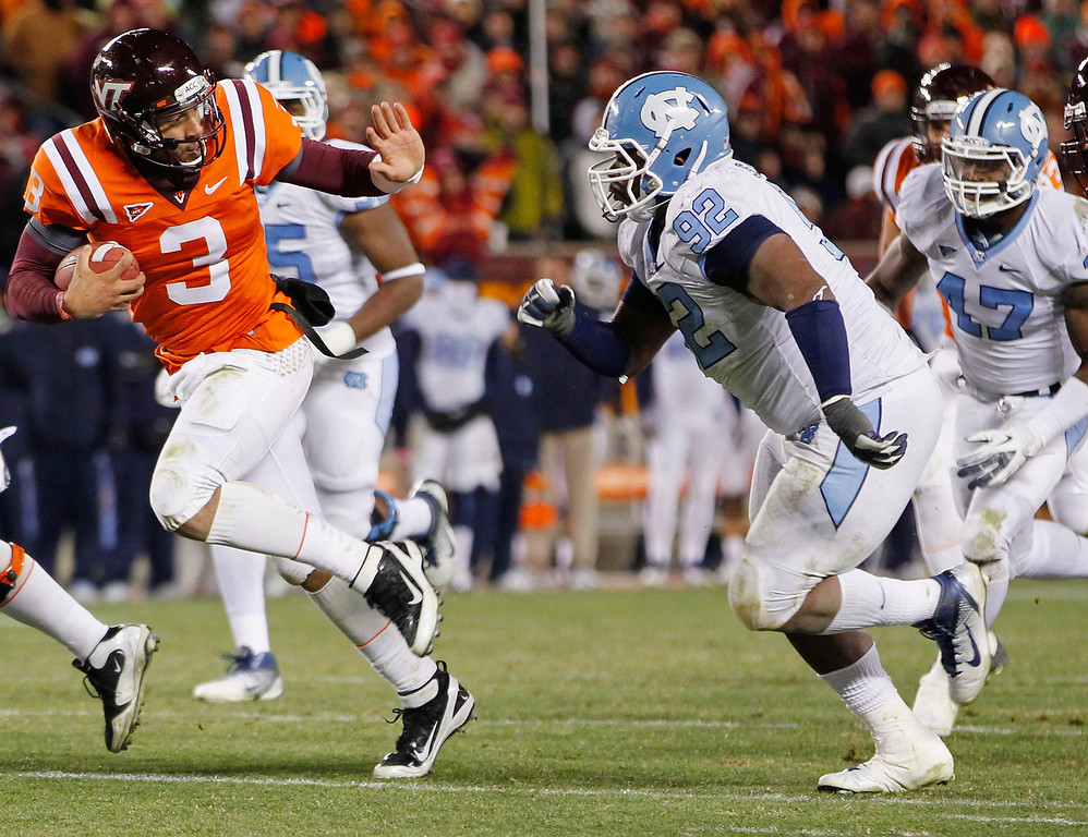 . North Carolina defensive tackle Sylvester Williams chases down Virginia Tech quarterback Logan Thomas #3  at Lane Stadium on November 17, 2011 in Blacksburg, Virginia. Williams was selected 28th by the Denver Broncos in the 2013 NFL Draft. (Photo by Geoff Burke/Getty Images)