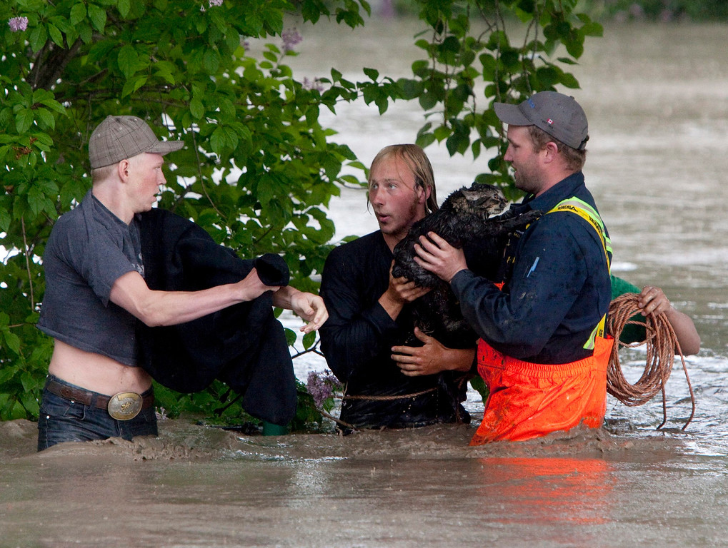 . Kevan Yaets, center, and his cat Momo are led to safety after flood waters submerged his truck in High River, Alberta on Thursday, June 20, 2013 after the Highwood River overflowed its banks. Calgary city officials say as many as 100,000 people could be forced from their homes due to heavy flooding in western Canada, while mudslides have forced the closure of the Trans-Canada Highway around the mountain resort towns of Banff and Canmore. (AP Photo/The Canadian Press, Jordan Verlage)