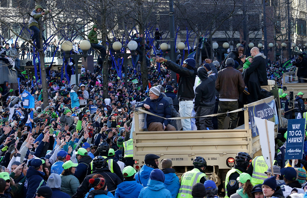 . Seattle Seahawks\' cornerback Richard Sherman, center, gestures to fans during the Super Bowl champions parade, Wednesday, Feb. 5, 2014, in Seattle.  (AP Photo/Ted S. Warren)