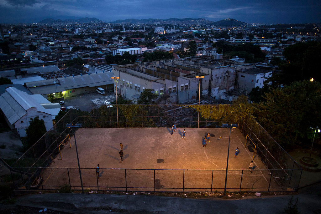 . In this Monday, June 2, 2014 photo, youth play soccer in the Mangueira slum of Rio de Janeiro, Brazil. Less than half a kilometer separates the sprawling slum from the Maracana stadium, but residents will be following the World Cup on television due to tickets being expensive and hard to come by. (AP Photo/Leo Correa)