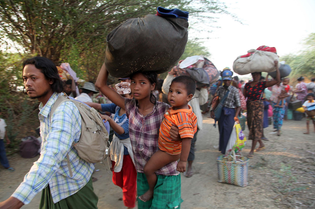 . Carrying belongings Muslims refugees try to move a rescue camp in Meikhtila about 550 kilometers (340 miles) north of Yangon, Myanmar, Friday, March 22, 2013.  Myanmar\'s president declared a state of emergency Friday in a central city shaken by sectarian bloodshed that has killed at least 20 people, as thousands of minority Muslims fled and overwhelmed riot police crisscrossed the still-burning town seizing machetes and hammers from enraged Buddhist mobs. Black smoke and flames poured from destroyed buildings in Meikhtila, where the unrest between local Buddhist and Muslim residents erupted Wednesday, the latest challenge to Myanmar\'s ever-precarious transition to democratic rule.(AP Photo/Khin Maung Win)